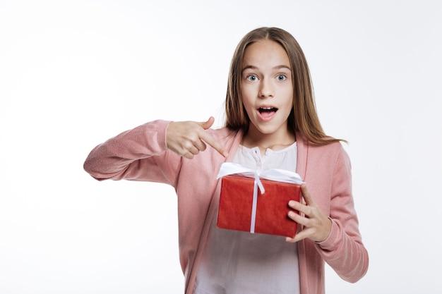 내용이 궁금하다. 선물 상자를 들고 그녀의 손가락으로 가리키는 즐거운 십 대 소녀