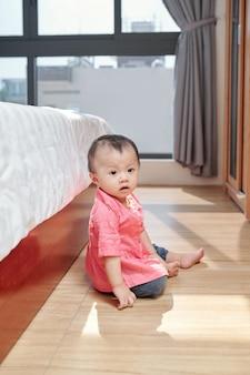 분홍색 셔츠에 호기심이 사랑스러운 어린 소녀가 바닥에 크롤링하고 아파트를 탐험