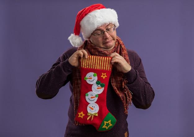 Curioso uomo adulto con gli occhiali e cappello da babbo natale con sciarpa intorno al collo che tiene la calza di natale guardando dentro isolato su parete viola