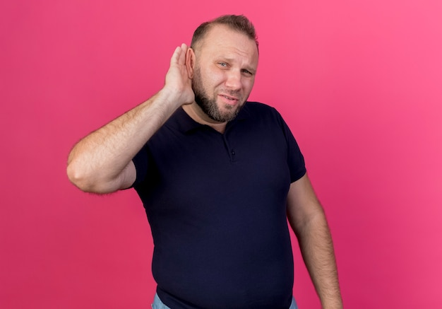 Curious adult slavic man doing can't hear you gesture isolated