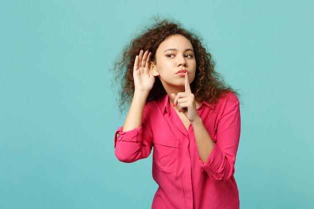 호기심 많은 아프리카 소녀는 청록색 배경에 격리된 입술에 손가락을 대고 쉿 소리를 내며 청력을 엿듣습니다. 사람들은 진심 어린 감정, 라이프 스타일 개념입니다. 복사 공간을 비웃습니다.