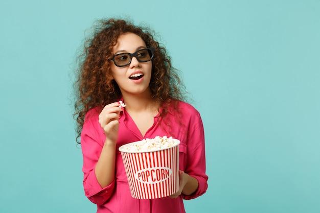 3d 아이맥스 안경을 쓴 호기심 많은 아프리카 소녀가 영화를 보고 스튜디오의 파란색 청록색 벽 배경에 격리된 팝콘을 들고 있습니다. 영화, 라이프 스타일 개념에서 사람들의 감정. 복사 공간을 비웃습니다.