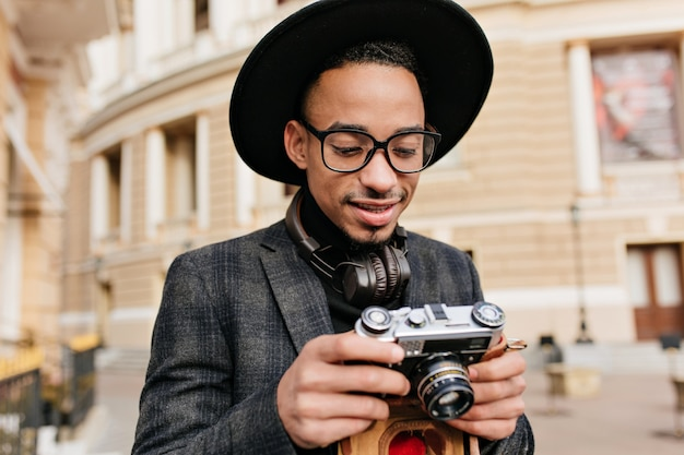 Curious african man in hat looking at camera. outdoor portrait of black male photographer standing near beautiful building.