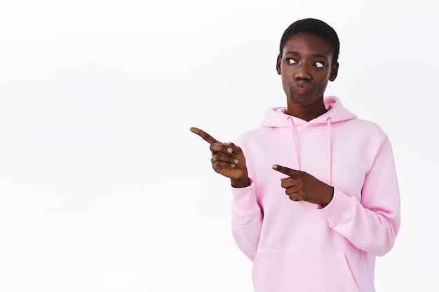 Любопытная и нерешительная привлекательная афроамериканка в стильной розовой толстовке с капюшоном, указывая на покупки и глядя влево, размышляя