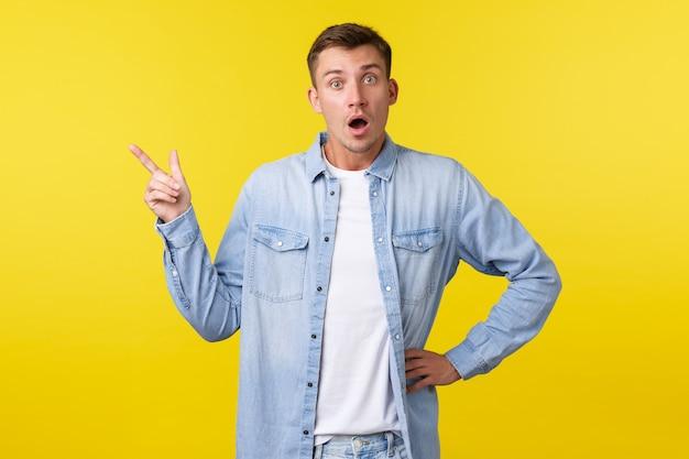 흥미롭고 흥미로운 금발 남자가 신제품이나 서비스에 대해 질문하고 왼쪽 상단 모서리를 가리키고 카메라를 쳐다보며 프로모션 제안, 노란색 배경에 대해 논의합니다.