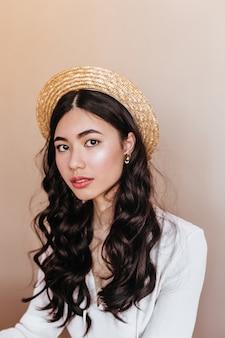 カメラを見て麦わら帽子の好奇心旺盛なアジアの女性。ベージュの背景に分離された巻き毛の中国人女性のスタジオショット。