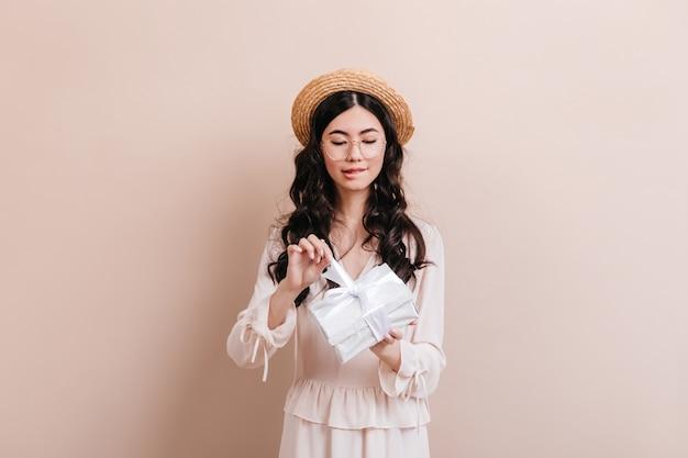 생일 선물을 여는 호기심 아시아 여자. 베이지 색 바탕에 선물을 들고 귀여운 중국 여성 모델.