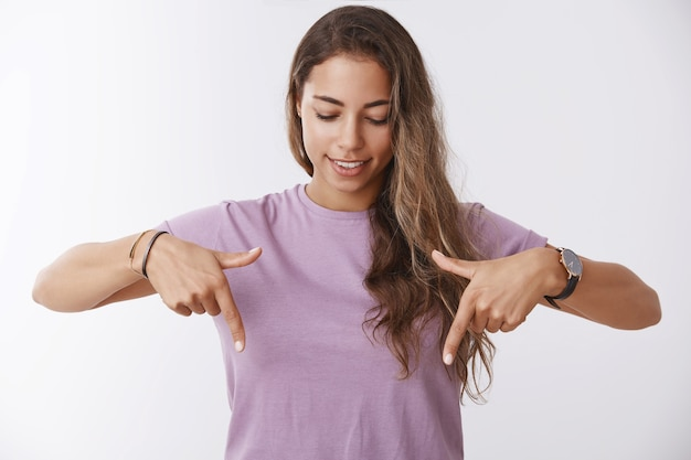 人差し指を下に向けて見下ろす紫色のtシャツを着た好奇心旺盛な魅力的な若い日焼けした女性は、面白がって笑って、興味をそそる素晴らしいプロモーションを下向きに見つけて、あなたに良いプロモーションを見せます