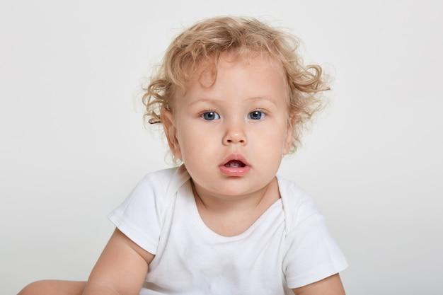 카메라를 직접보고, 그의 두 이빨을 보여주는 호기심이 아기, 티셔츠를 입고