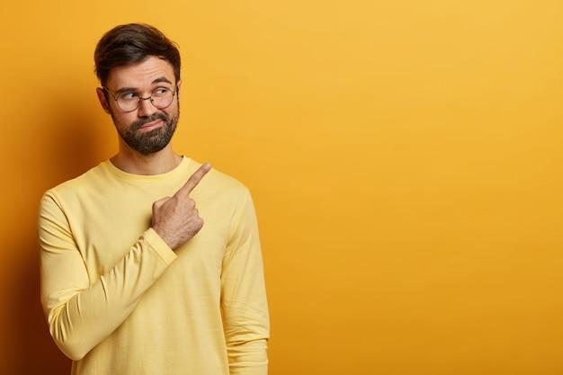 L'uomo barbuto curioso indica lo spazio della copia sul muro giallo, mostra informazioni importanti, trova una soluzione o una risposta alla domanda, dice il suo suggerimento, indossa un maglione giallo, occhiali rotondi
