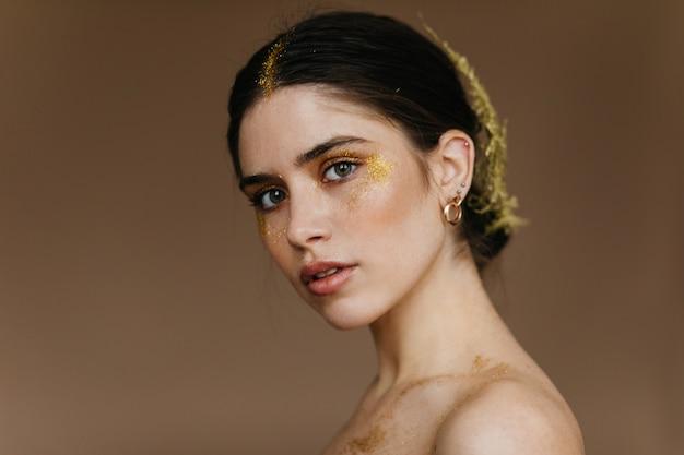 호기심 많은 아름다운 여인이 보석을 착용합니다. 갈색 벽에 포즈 긍정적 인 로맨틱 여자입니다.