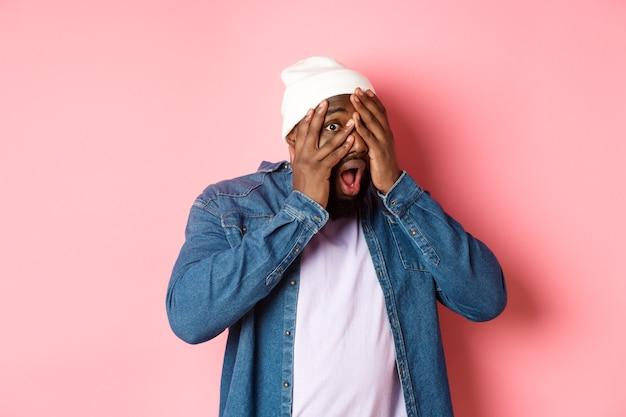 Curioso uomo nero copre gli occhi ma sbircia tra le dita, fissa la telecamera stupita, in piedi in berretto hipster su sfondo rosa