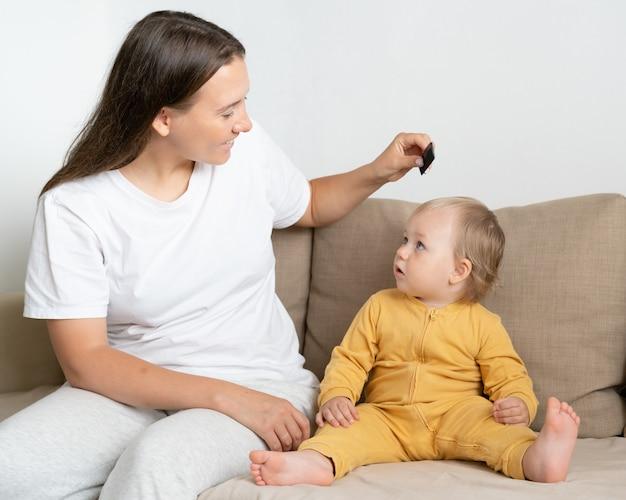 Любопытный белокурый ребенок смотрит на мать, расчесывающую детские волосы с расческой в руке