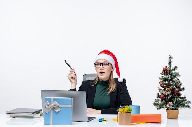 Любопытная блондинка в шляпе санта-клауса сидит за столом с елкой и подарком на ней сосредоточилась на чем-то на белом фоне