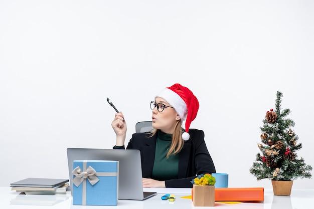 Любопытная блондинка в шляпе санта-клауса сидит за столом с елкой и подарком на ней, глядя на что-то на белом фоне