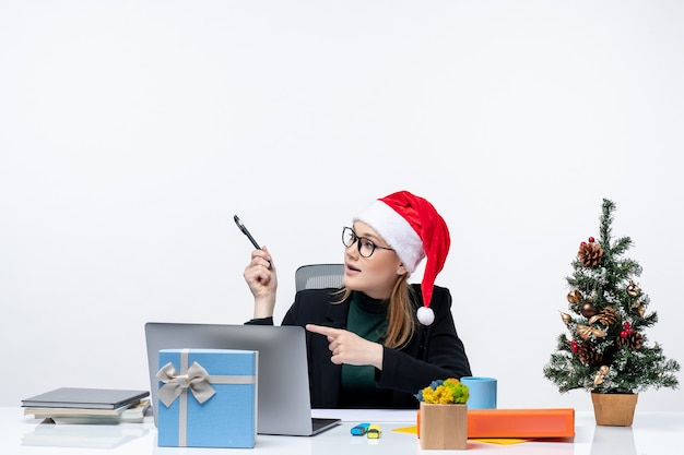 Curious blonde woman with a santa claus hat sitting at a table with a christmas tree and a gift on it looking at something on the left side on white background