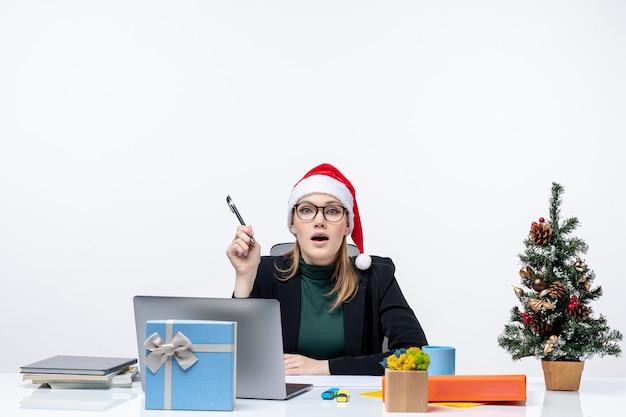 Curiosa donna bionda con un cappello di babbo natale seduto a un tavolo con un albero di natale e un regalo su di esso su sfondo bianco