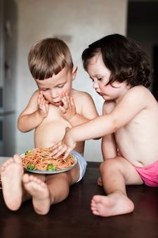 Любопытный мальчик и девочка едят макароны