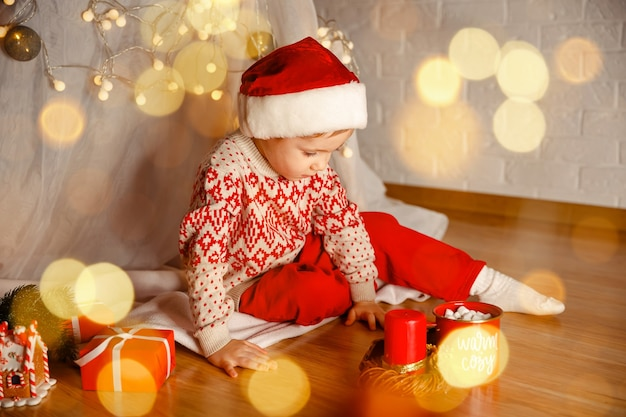 Curious boy peeks inside a xmas present child kid with red gift box