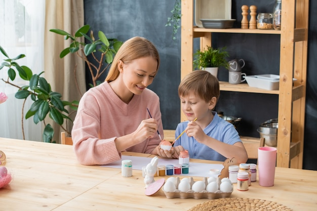 Curious boy sitting at wooden table and painting eggs with gouache while spending time with mother