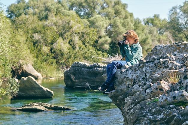 호수 근처 바위 해안에 앉아 사진을 찍는 호기심 소년