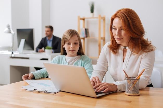 그녀의 엄마가 보고서에서 작업하고 필요한 다이어그램을 그녀에게 건네주는 호기심이 밝은 생산적인 소녀