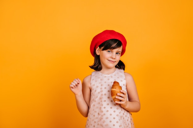 Curious brunette kid posing on yellow wall.  preteen girl eating croissant.
