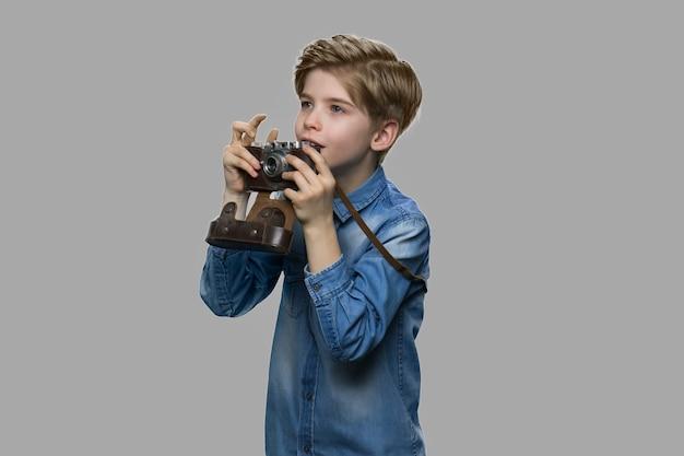 쌍안경을 사용하여 호기심이 백인 소년. 회색 배경에 쌍안경을 사용하는 귀여운 아이 소년 데님 셔츠. 여행 개념.