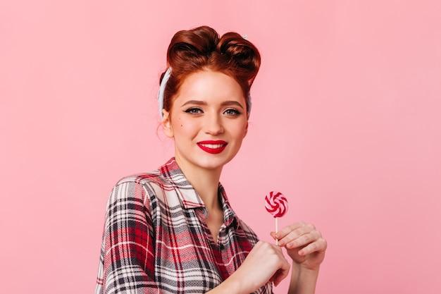 カメラを見ているロリポップを持つ好奇心旺盛な白人女性。ピンクのスペースで隔離のキャンディーとかわいいピンナップガールの正面図。