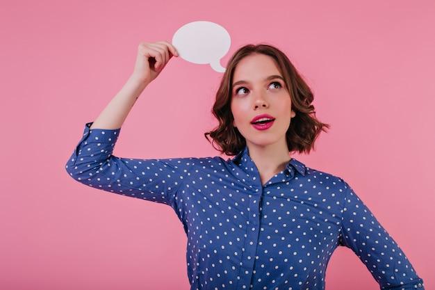 優しい笑顔でポーズをとる青いブラウスの好奇心旺盛な魅力的な女性。ピンクの壁に何かを考えている陽気な白人の女の子。