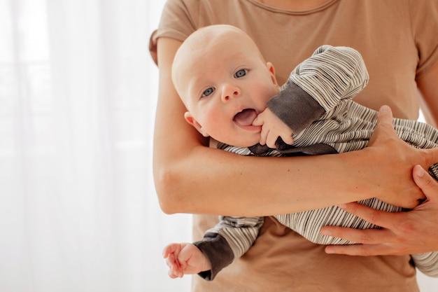 Любопытный нахальный малыш на руках мамы