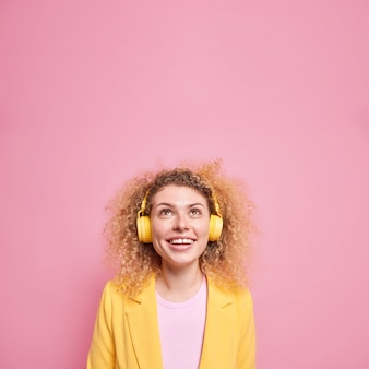 Curious cheerful woman with curly hair focused above has broad smile wears stereo headphones on ears listens music from favorite playlist dressed in stylish clothesisolated over pink wall