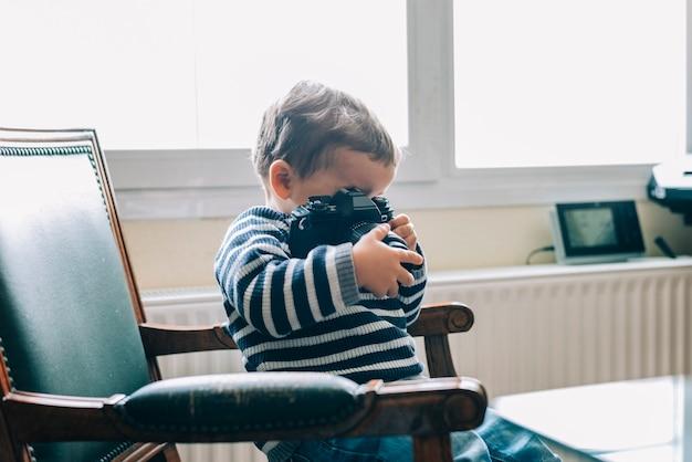 Любопытный ребенок изучает камеру, сидя на стуле