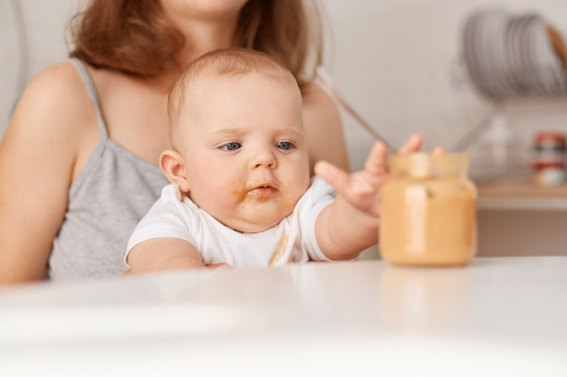 Curious child stretching out arm to feed jar, faceless mother feeds her little infant daughter with vegetable puree, sitting at table at home, feeding up.