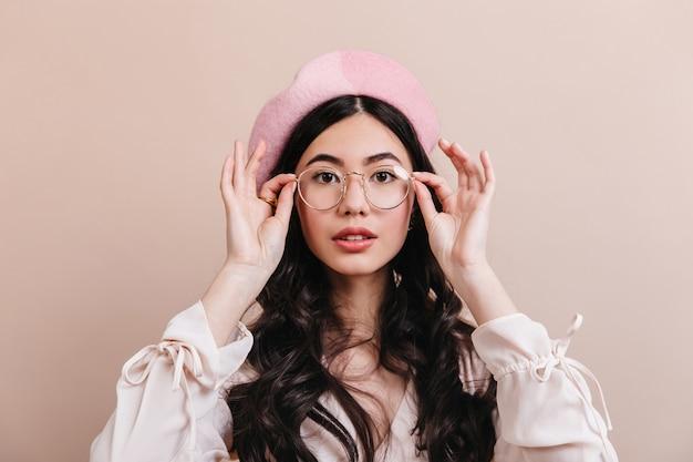 眼鏡をかけてポーズをとる好奇心旺盛な中国人女性。ベージュの背景に分離されたベレー帽のファッショナブルなアジアの女性。
