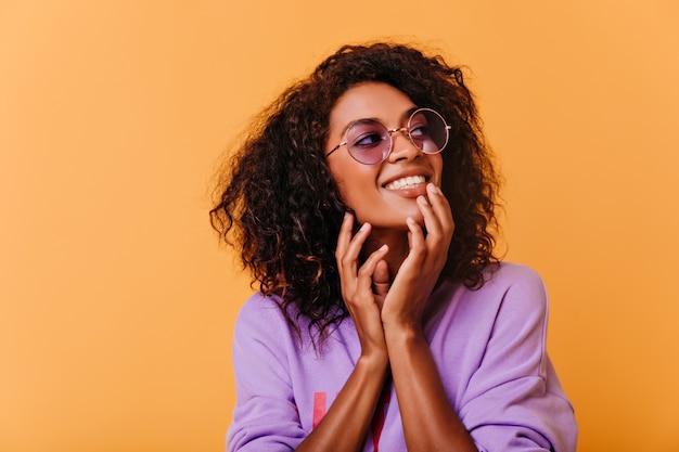 紫色のメガネのポーズで好奇心旺盛なかわいい女の子。ポジティブな感情を表現する至福のアフリカの女性の屋内ショット。
