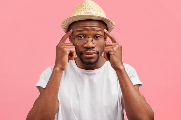 Любопытный темнокожий мужчина средних лет держит указательные пальцы на висках
