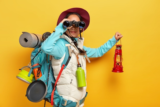 Curious female backpacker explores tourist destination, uses binoculars, dressed in active wear, holds kerosene lamp carries travelling items with rucksack