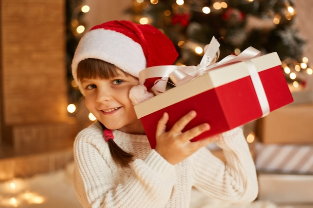 Curious female child wearing white sweater and santa claus hat, shaking gift box, being interested what inside, posing in festive room with fireplace and xmas tree.
