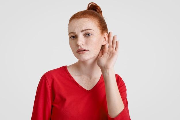 好奇心が強いそばかすのある若い女性の生姜のパンは耳の近くに手を置いて、機密情報を聞き取ろうとします。