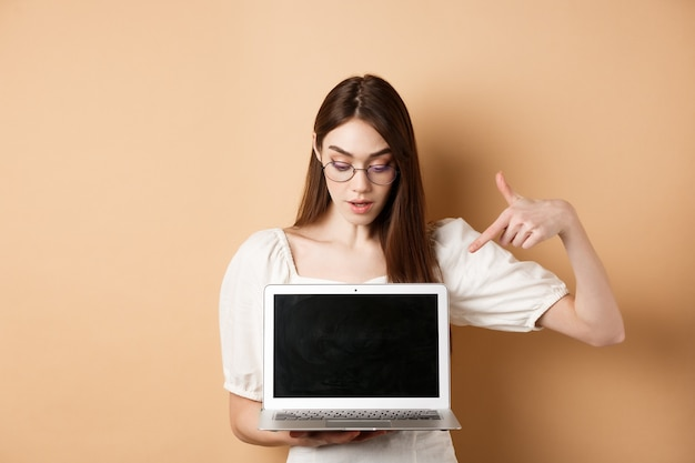 Curious girl in glasses pointing at laptop screen, check out online deal, demonstrate project on computer, standing on beige background.