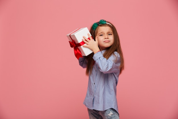 Curious girl shaking present gift-wrapped box close to ear trying to determine what's inside