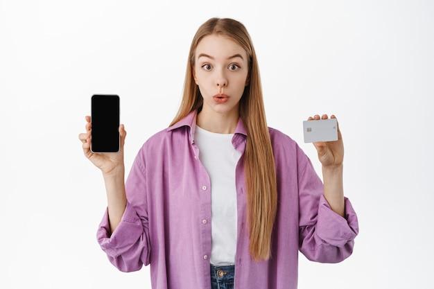 好奇心旺盛な女の子がクレジットカードとスマートフォンの空白の画面を表示し、正面を見て驚いて驚いて、オンラインで買い物をし、白い壁の上に立っています