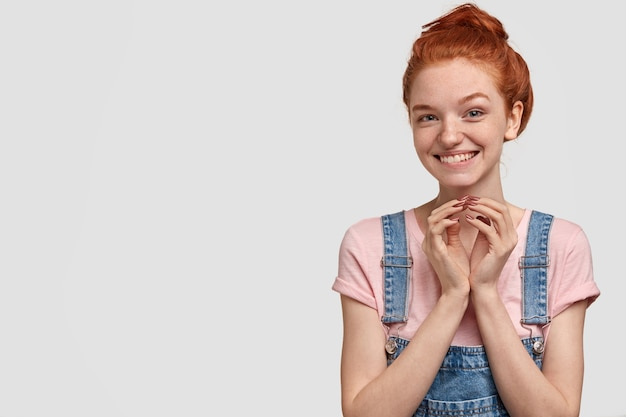 Curious glad teenage girl with freckled skin, ginger hair, keeps hands together, looks with cunning expression, waits for help, dressed in overalls, isolated over white wall, free space aside