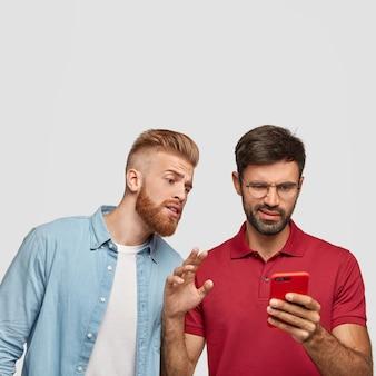生姜の散髪とあごひげを生やした好奇心旺盛な男が友人のスマートフォンを覗く