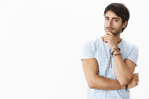 Curious handsome businessman talking to partner listening ideas holding hands on chin with thoughtful expression looking at front as thinking over grey wall