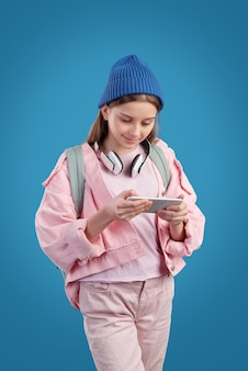 Curious hipster teenage girl in pink jacket wearing wireless headphones on neck watching video on phone