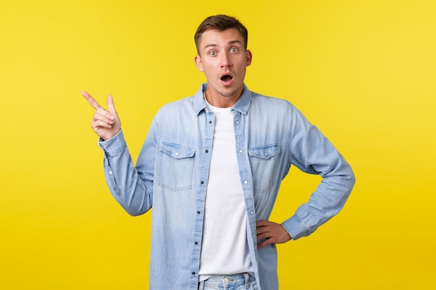 Curious and interested handsome blond guy asking question about new product or service, pointing upper left corner and looking intrigued at camera, discussing promo offer, yellow background.