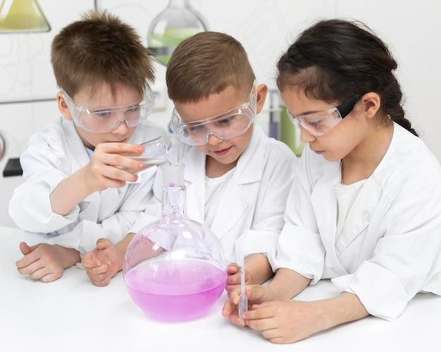 Bambini curiosi che fanno un esperimento chimico a scuola