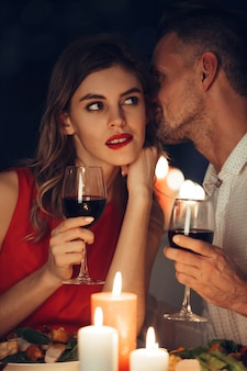 Curious lady in dress red with glass of wine listening her handsome man